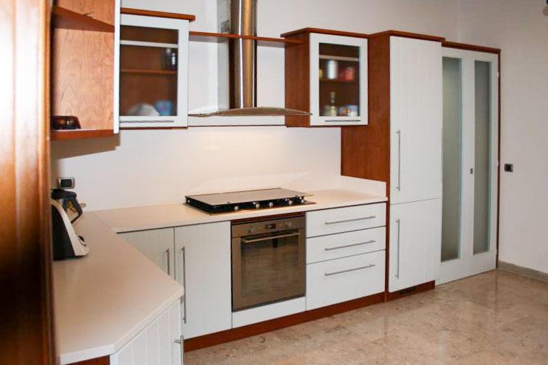 Cucina due colori con vano ripostiglio chiuso con porta a libro realizzata su misura il legno e vetri opachi.